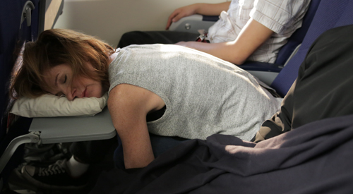 A woman demonstrating how to sleep on a plane